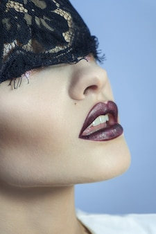 Young sensual lady with beautiful lips and black lace on eyes in studio