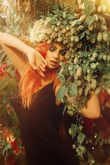 頭にホップと屋外でポーズをとる森の目を閉じた若い官能的な赤毛の女性