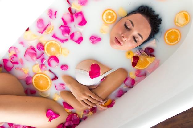 ミルクとバラの花びらと若い官能的な女性ブルネットltaking風呂