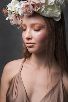 Young sensual woman in dress with beautiful flower wreath