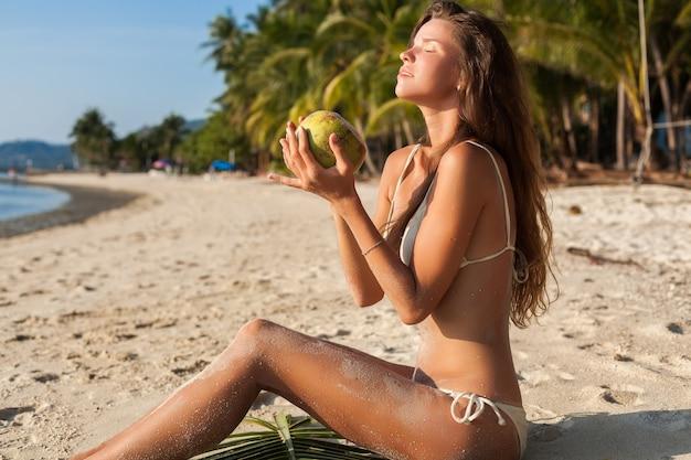 Young sensual woman in white bikini swimwear holding coconut, smiling, sunbathing on tropical beach.