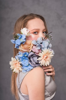Young sensual woman with beautiful flower composition