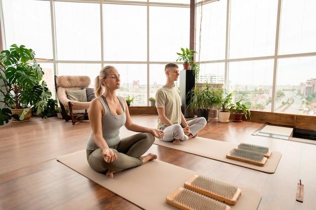 Молодая безмятежная пара в спортивной одежде, сидящая в позе лотоса на циновках, вместе выполняя упражнения для медитации в домашней обстановке