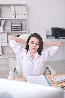 Молодая спокойная женщина-офис-менеджер расслабляется в кресле за столом, держа руки за головой и наслаждаясь перерывом