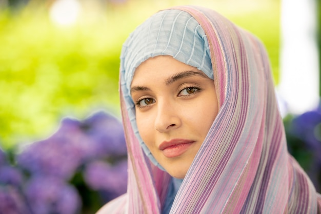 Young serene female in traditional hijab looking at you while spending time in urban environment