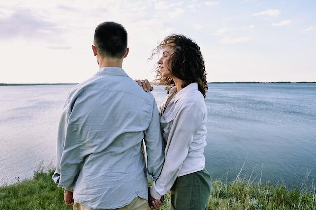 Молодая безмятежная женщина с темными вьющимися волосами стоит рядом со своим мужем, пока обе отдыхают у большого озера на фоне облачного неба.