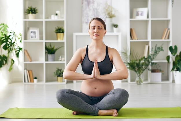 Young serene future mother keeping balance while sitting on mat in pose of lotus with her hands put together by chest at home