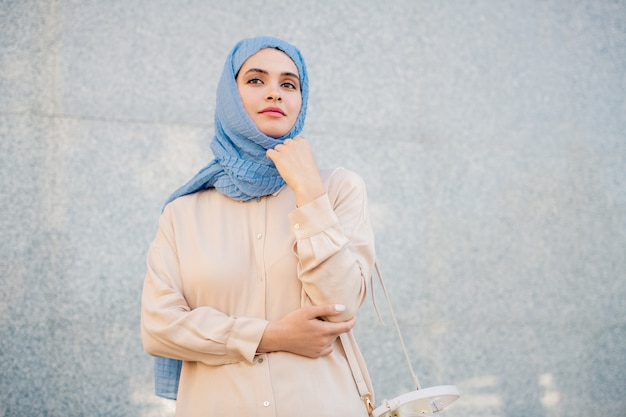 Young serene woman in hijab and casualwear standing by wall of modern building in urban environment