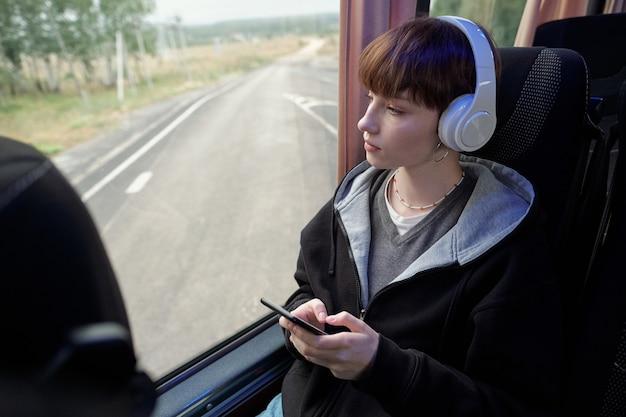 Молодая спокойная женщина в наушниках, глядя через окно автобуса