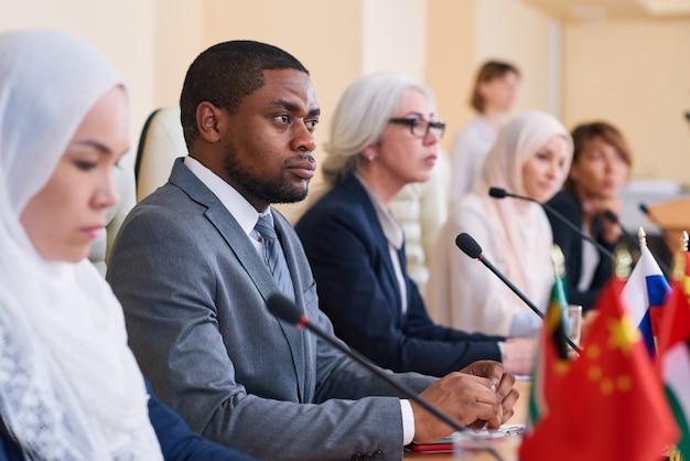 若いアフリカ系アメリカ人の深刻なビジネスマン、会議の参加者、スピーカーのレポートの1つに注意深く耳を傾ける