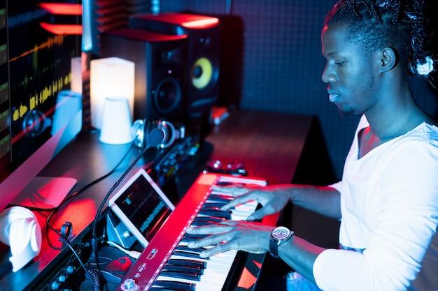 Молодой серьезный афроамериканец делает новую музыку, сидя в студии перед доской и нажимая клавиши