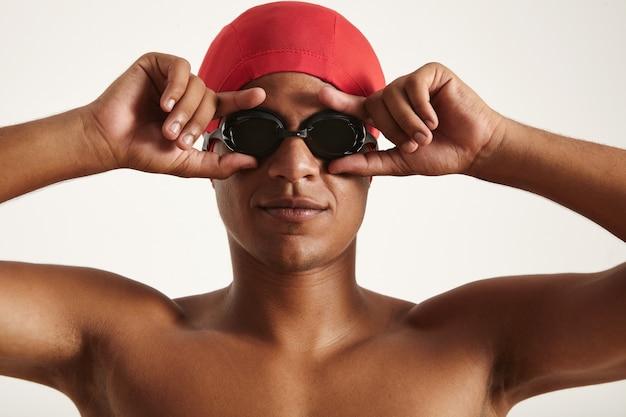 Молодой серьезный афро-американский пловец в красной шапочке, надевающий черные плавательные очки на белом