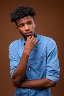 Young serious african man thinking on brown