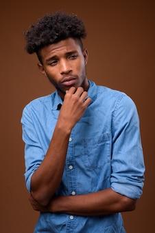 Молодой серьезный африканский мужчина думает о коричневом