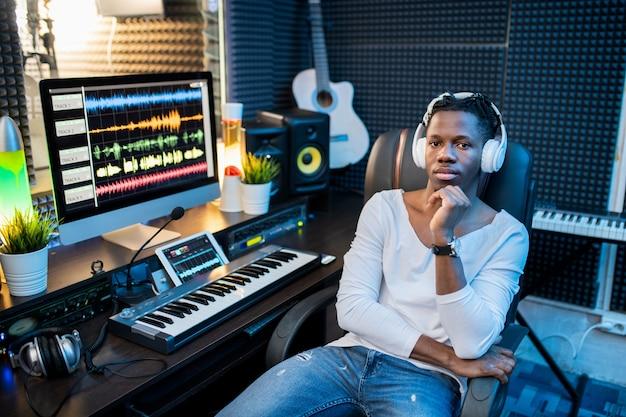 Молодой серьезный африканский музыкант в повседневной одежде и наушниках сидит
