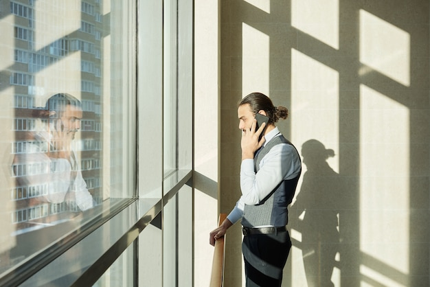 Young serious agent or broker in formalwear standing by window inside large business center and consulting clients on smartphone
