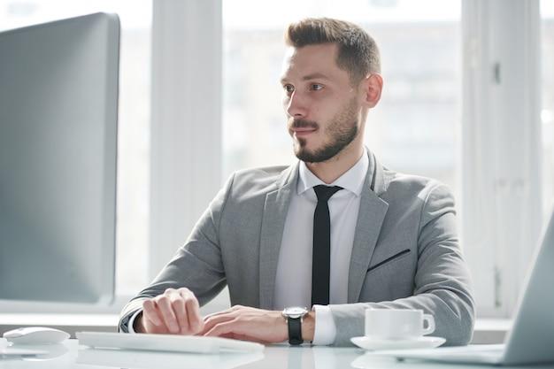 Молодой серьезный аналитик в официальной одежде, глядя на экран компьютера, сосредоточившись на сети