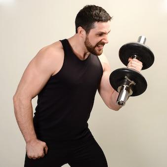 젊은 심각한 운동 선수는 팔뚝을 개발하기 위해 아령으로 운동을 수행합니다.