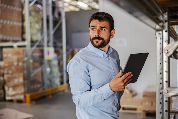 Young serious attractive bearded supervisor standing in warehouse and using tablet.