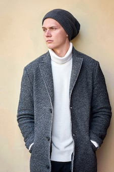 Young serious attractive hipster trendy man wearing a gray coat, white sweater and black jeans. portrait. outdoors.