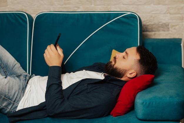 ネットサーフィンをしている真面目なひげを生やした若い男が、ソファに横になって自宅で携帯電話でニュースを読んでいます。