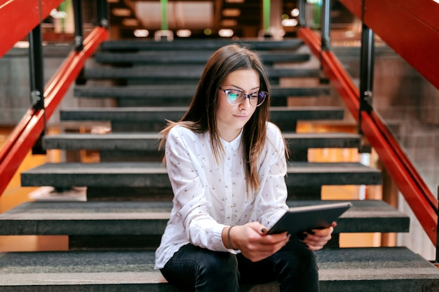 Young serious beautiful female teacher sitting on the stairs and using tablet while waiting for class to begin.