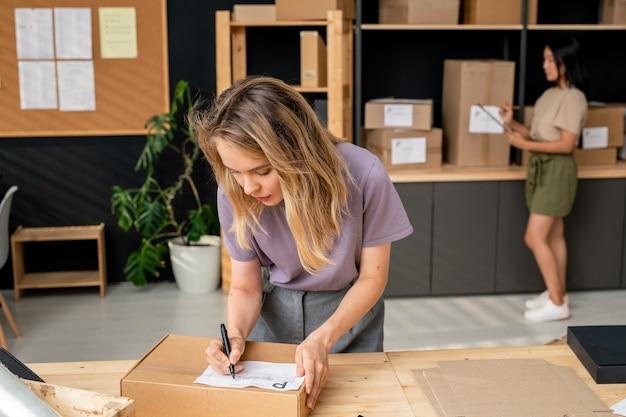 Молодая серьезная блондинка-менеджер интернет-магазина записывает адрес получателя на упакованной коробке, стоя у стола и наклоняясь над ним