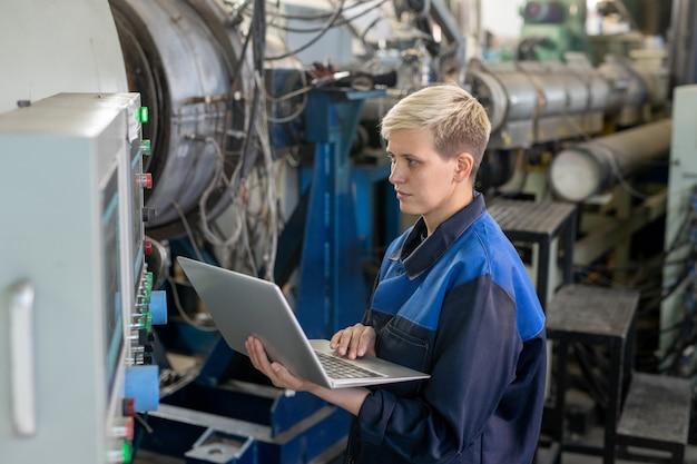 작업장에서 산업 장비에 대한 온라인 기술 데이터를 살펴보는 동안 랩톱을 사용하는 작업복을 입은 젊은 진지한 금발 여성 노동자