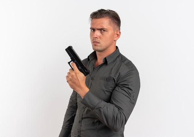 Молодой серьезный блондин красавец держит пистолет на белом фоне с копией пространства