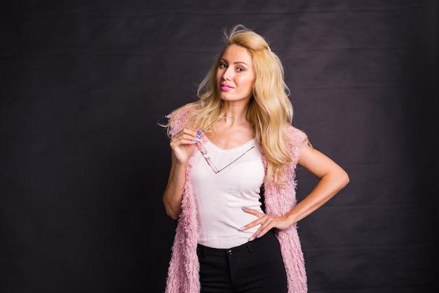 Молодая серьезная блондинка в розовом пальто