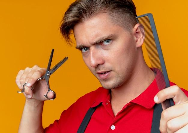 制服を着た若い深刻な金髪の男性の床屋は、櫛とはさみを保持します