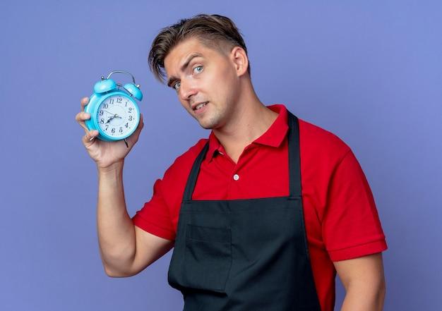 Il giovane barbiere maschio biondo serio in uniforme tiene la sveglia isolata sullo spazio viola con lo spazio della copia