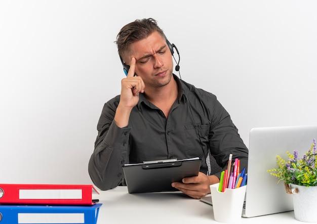 L'uomo di giovane lavoratore di ufficio biondo serio con le cuffie si siede alla scrivania con strumenti di ufficio utilizzando laptop tiene e guarda negli appunti