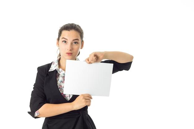 Молодая серьезная брюнетка бизнес-леди в униформе с белым плакатом в руках, изолированные на белой стене