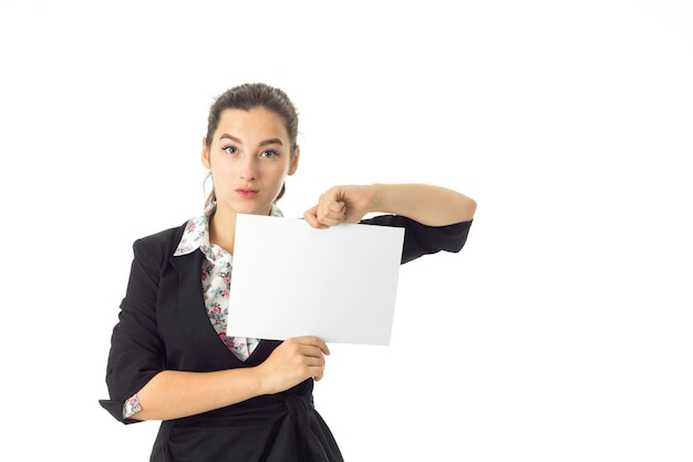 Young serious brunette business woman in uniform with white placard in hands isolated on white wall