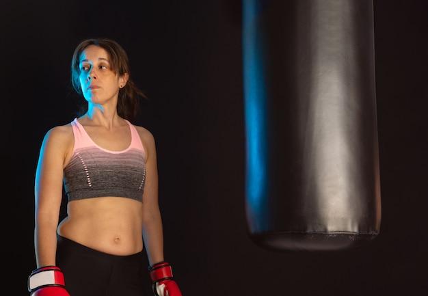 青い側面照明と黒い壁とサンドバッグの横に赤いボクシンググローブと立っているポニーテールの若い深刻なブルネットの少女