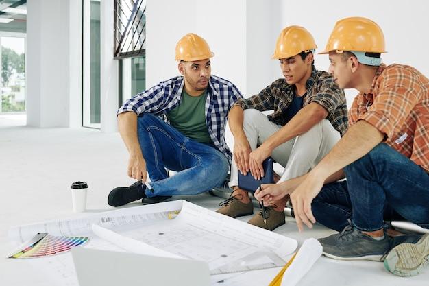 Молодые серьезные строители в касках сидят на полу и обсуждают, как отремонтировать квартиру