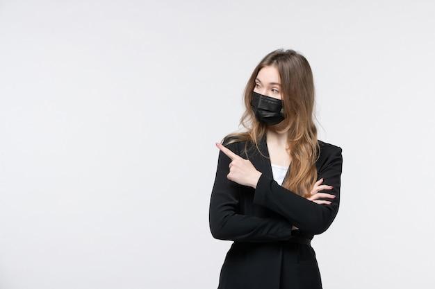 의료용 마스크를 쓰고 외진 흰 벽의 오른쪽에 있는 누군가를 가리키는 정장을 입은 젊은 진지한 비즈니스 여성