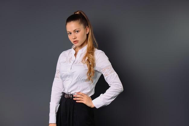 Молодая серьезная деловая женщина позирует на сером изолированном фоне