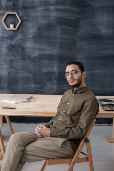 Young serious businessman in casualwear and eyeglasses sitting on chair by table on space of blackboard