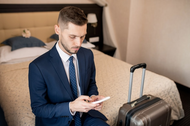 Young serious businessman in elegant suit looking through contacts in smartphone to call taxi while sitting on bed in hotel room