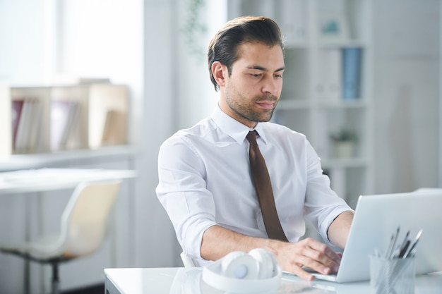 Young serious businessman in formalwear looking at laptop display by his workplace in office
