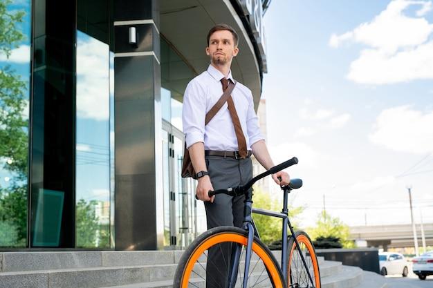 Молодой серьезный бизнесмен собирается поехать на велосипеде, стоя на фоне лестницы и экстерьера современного здания