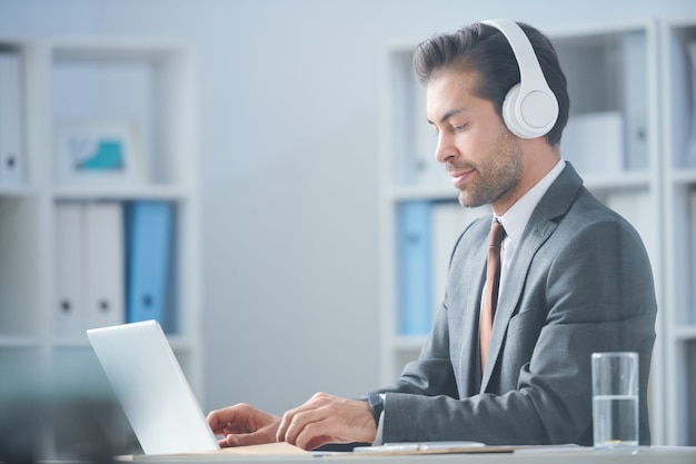 Young serious businessman in headphones watching online video about new business trends