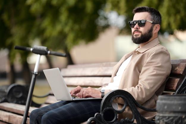 우아한 casualwear 및 선글라스 따뜻한 날에 공원에서 나무 벤치에 앉아 노트북에서 네트워킹에 젊은 심각한 사업가