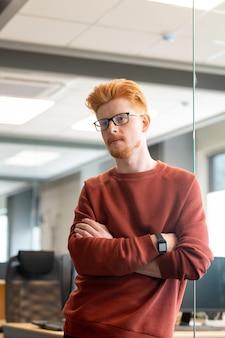 안경과 갈색 스웨터에 젊은 심각한 사업가 사무실의 유리 문에 서있는 동안 가슴에 팔을 교차 유지