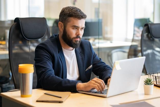 그의 직장에서 회의 또는 세미나에 대한 보고서를 준비하는 동안 노트북 디스플레이를보고 formalwear에서 젊은 심각한 사업가