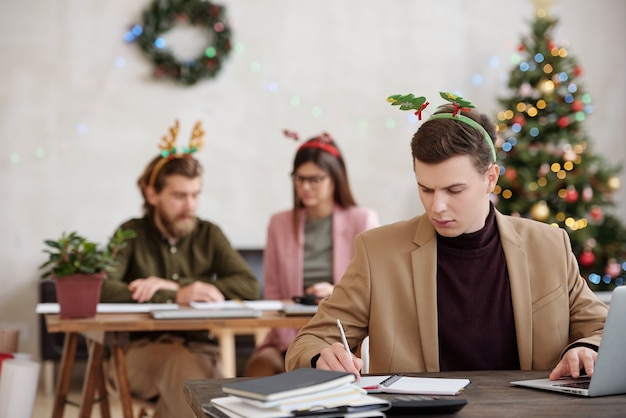크리스마스 이브에 노트북 앞에서 책상 옆에서 작업을 계획하는 동안 노트북에 메모를 하는 크리스마스 모자를 쓴 젊은 진지한 사업가