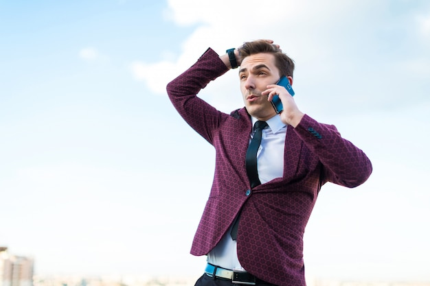 Young serious businessman in red suit and shirt with tie stand on the roof and talk on the phone