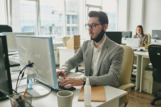 사무실에서 직장에서 입력하는 동안 컴퓨터 화면을보고 턱 아래 검은 보호 마스크와 젊은 심각한 사업가